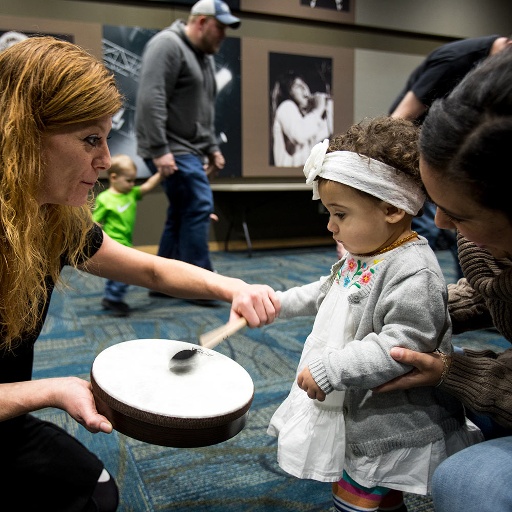 Photo: Instructor Rochelle Starnes helps another child to play a drum.