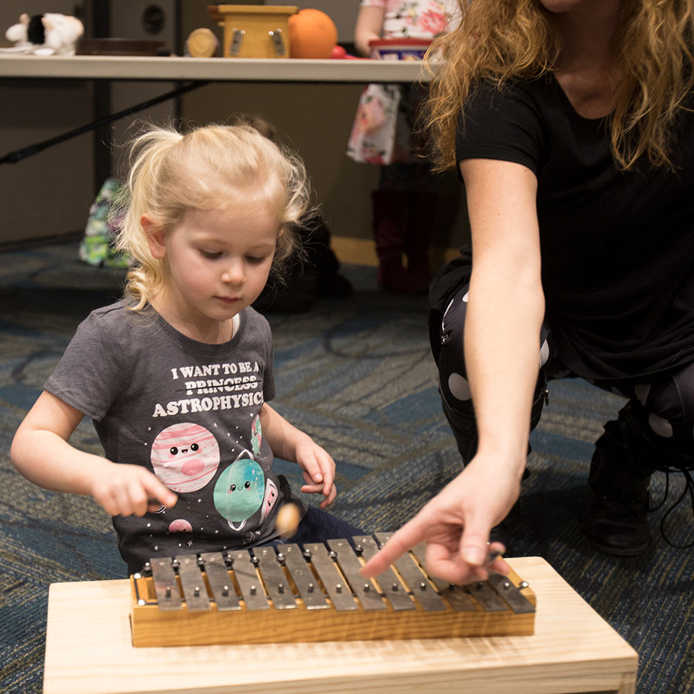 Photo: A child plays the xylophone, aided by Rochelle.