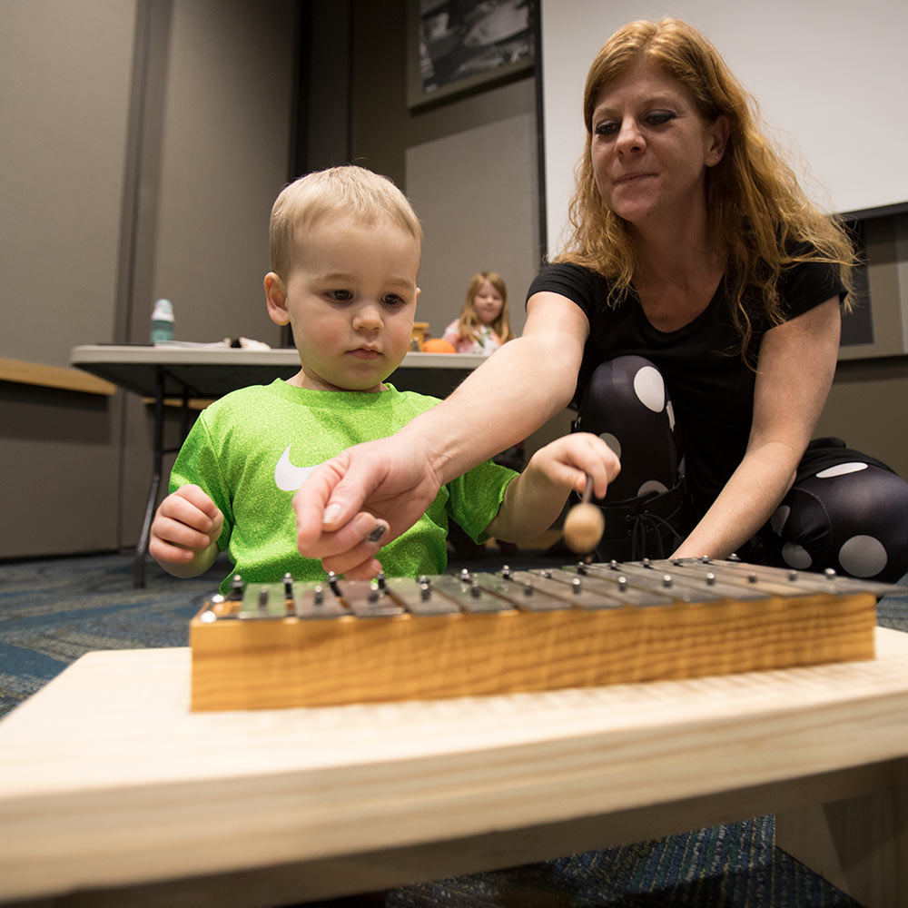 Photo: Rochelle helps another child learn to play the xylophone.