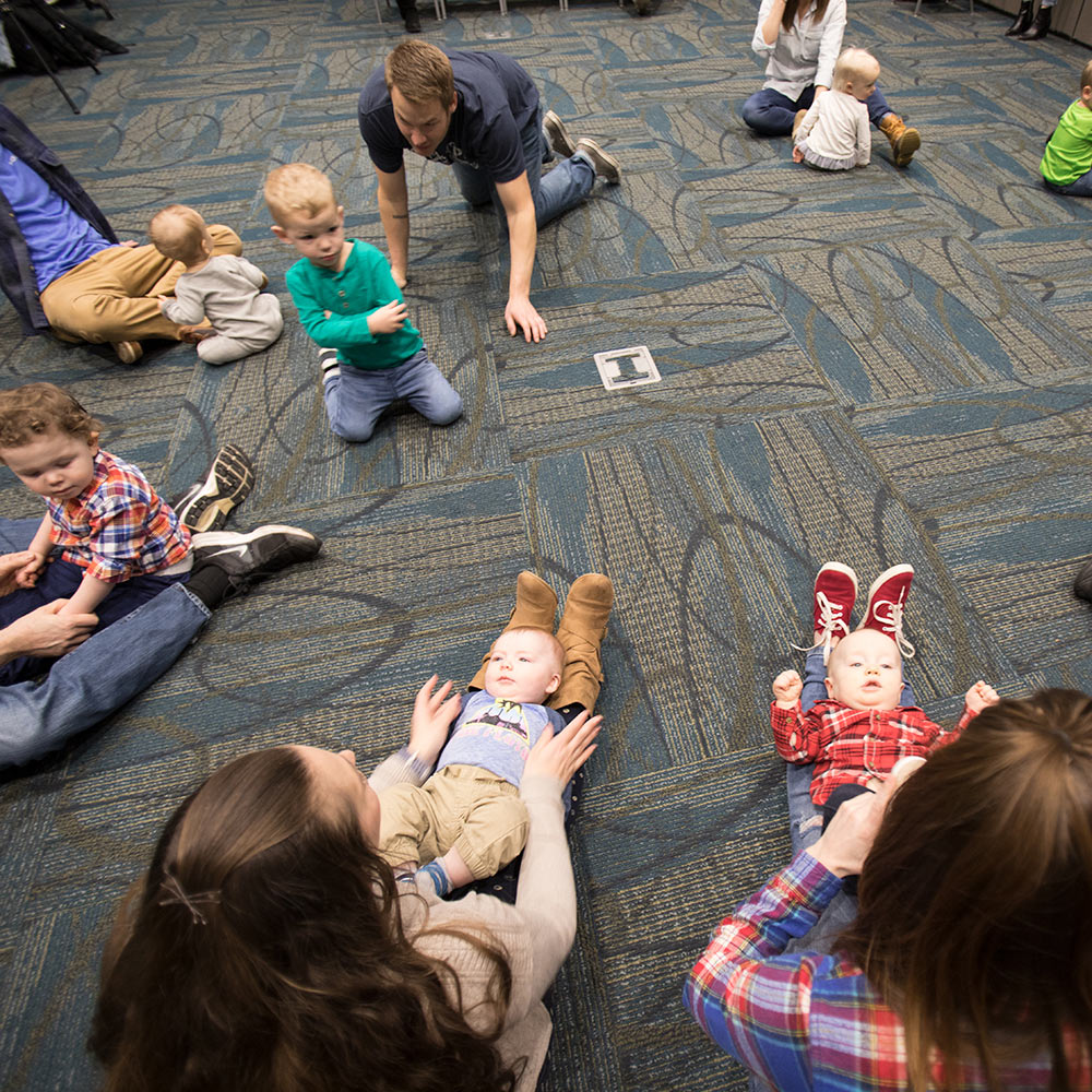 Photo: Parents and children sit in a circle.