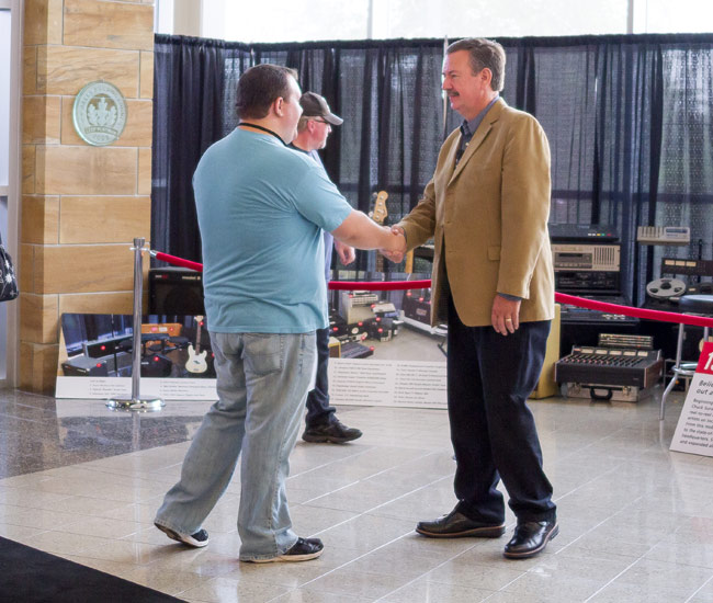 Chuck Surack shaking visitors hand
